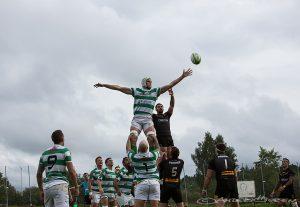 En grönvit spelare är högt upp i luften och tar bollen framför motståndaren.