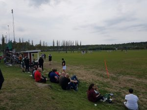 Många människor sittandes på gräs och läktare tittar på en rugbymatch.