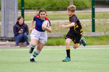 En person springer med en boll i famnen och är jagad av en annan person.
