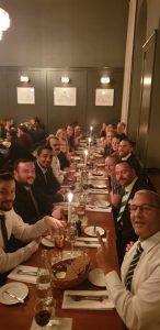 Män och kvinnor sitter vid ett bord och ser glada ut