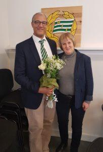 Hammarbys ordförande Kanogo Njuru står bredvid Py Börjesson från Hammarbyalliansens styrelse och håller i en bukett blommor.