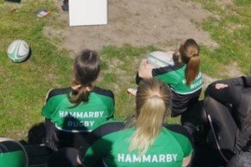 Personer med grönsvarta kläder sitter med ryggen mot kameran. De tittar på en tavla där en person står och ritar.