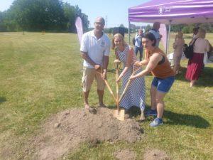 Tre personer står bredvid varandra och håller i en spade med tre ihopsatta handtag. Tillsammans gräver de i en jordhög.