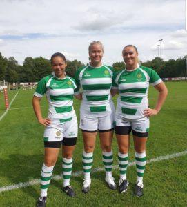 Tre tjejer står i grönvita tröjor och vita shorts. De ser glada ut.