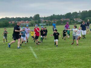 En vuxen person springer med en boll i händerna och flera barn försöker att stoppa honom.