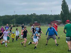 En pojke springer med bollen i famnen rakt mot vuxna personer.