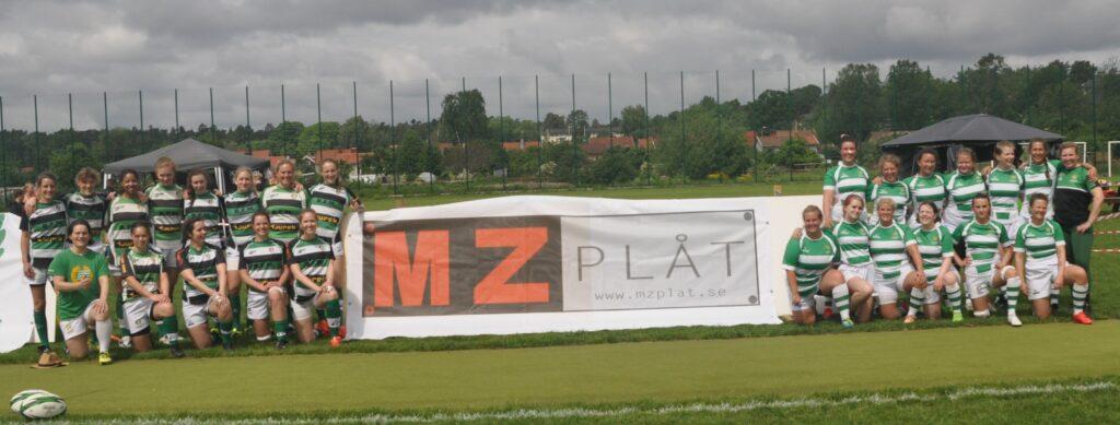 Två grupper av personer, klädda i olika Hammabytröjor, står uppställda på varsin sida av en skylt. På skylten står det MZ Plåt, vilket är en sponsor till lagen.