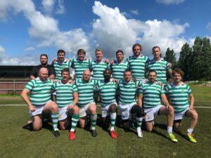Tretton personer står med grönvita tröjor och en person i svart. De håller armarna om varandras axlar.