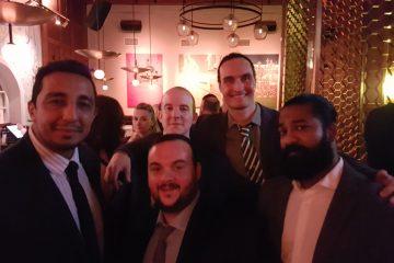 Fem män står framför kameran och ser glada ut